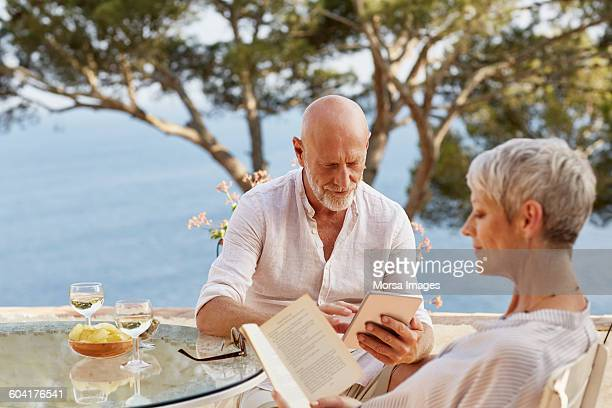 Man using digital table while woman reading book
