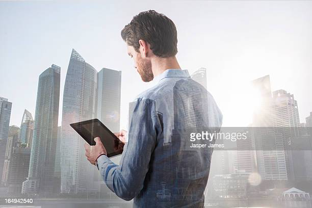 man using digital tablet and cityscape