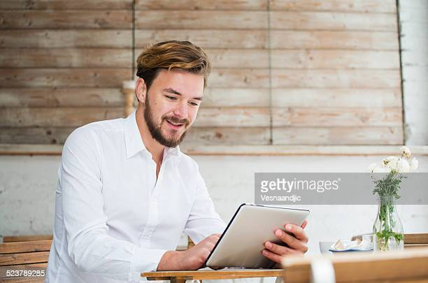 Mann mit digitalen tablet im Café