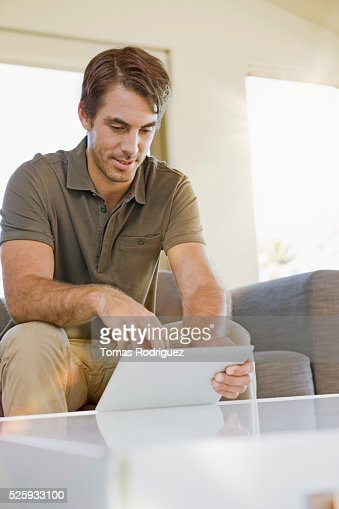 Man using digital tablet at home : Stock Photo