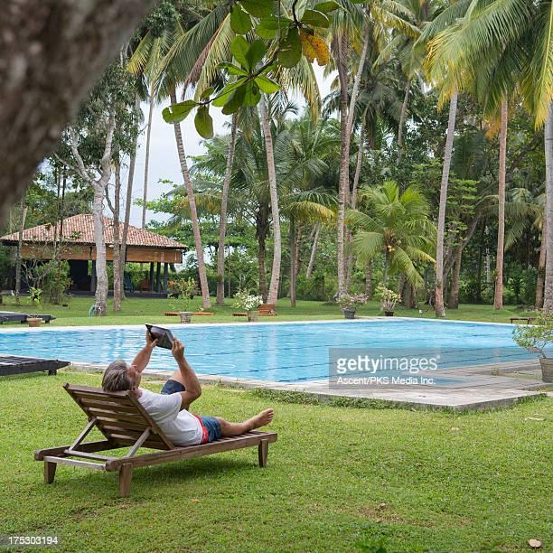 Man using digital tablet at pool, tropics