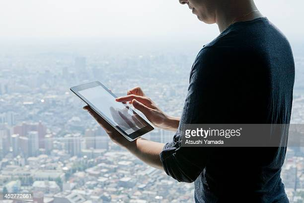 Man using digital tablet, cityscape in background