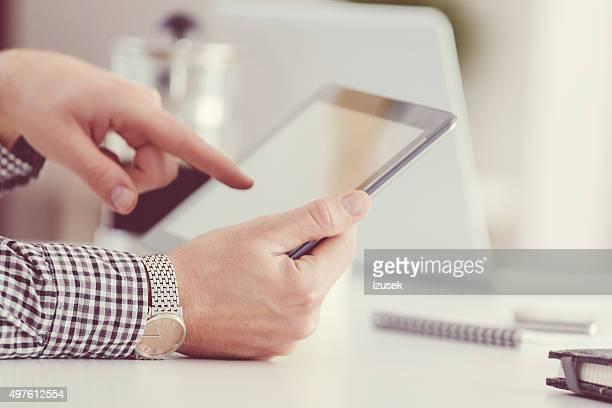 Homme à l'aide de tablette numérique, gros plan de mains, une personne méconnaissable