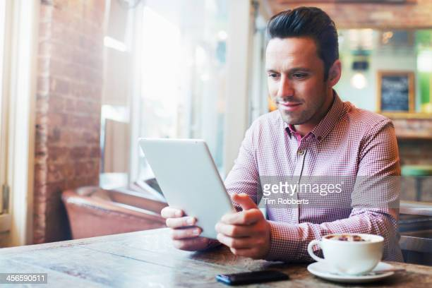 Man using digital tablet in cafe.