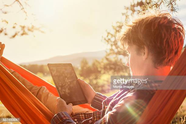 Man using digital tablet in hammock
