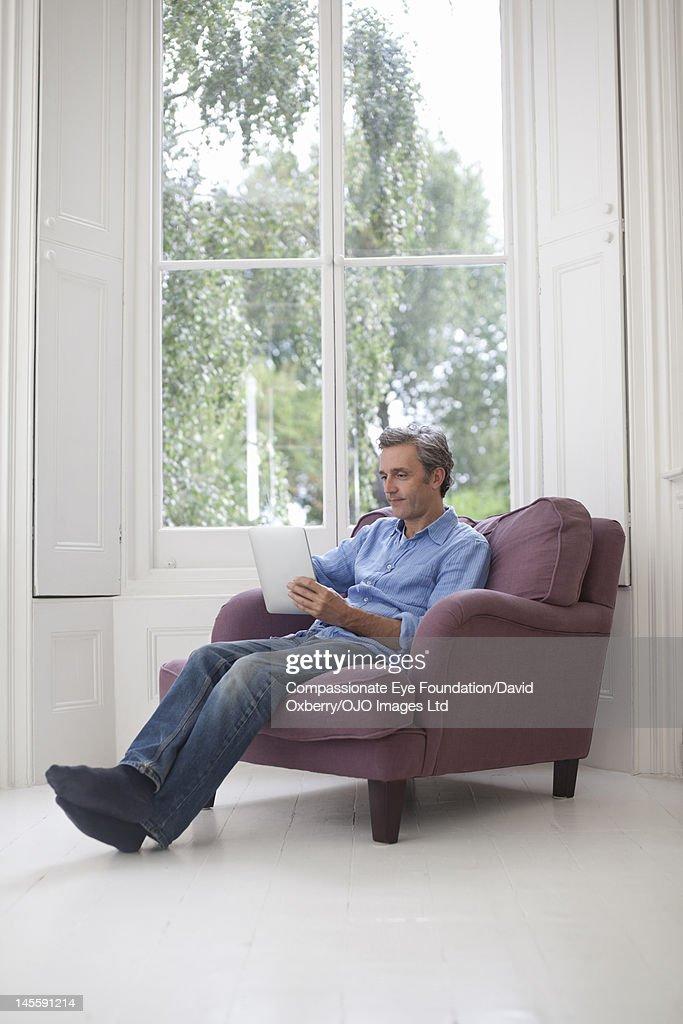 Man using digital tablet in living room : Stock Photo