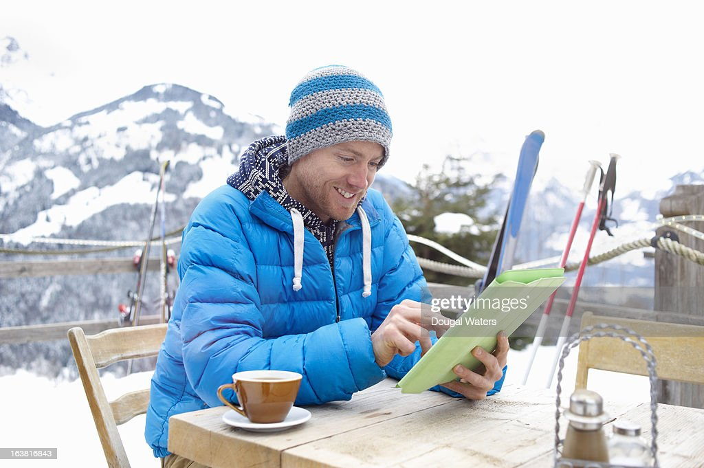 A man using digital tablet in ski destination. : Stock Photo