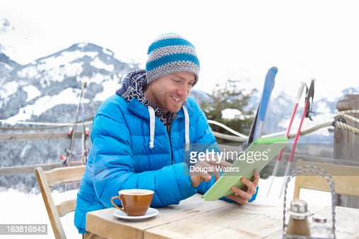 A man using digital tablet in ski destination.