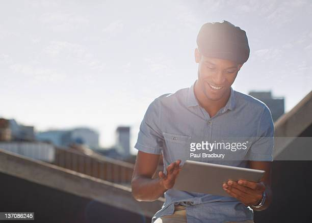 Man using digital tablet on sunny urban rooftop
