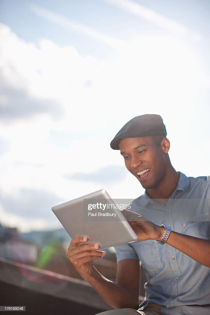 Man using digital tablet on sunny urban rooftop