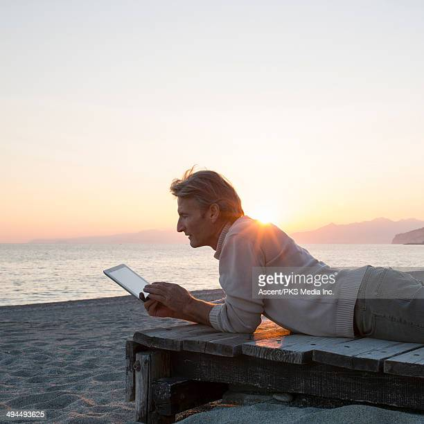 Man using digital tablet on wooden wharf, beach