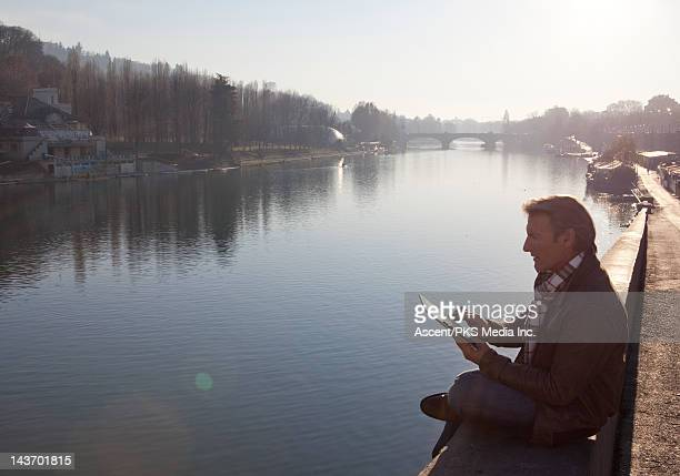 Man using digital tablet, overlooking a city river