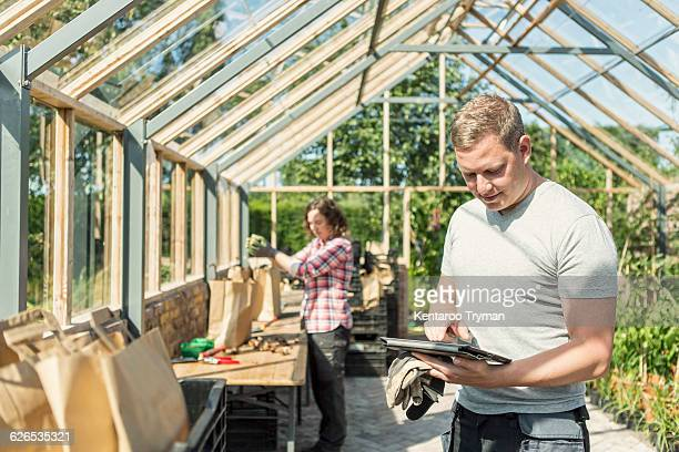 Man using digital tablet while woman working in greenhouse
