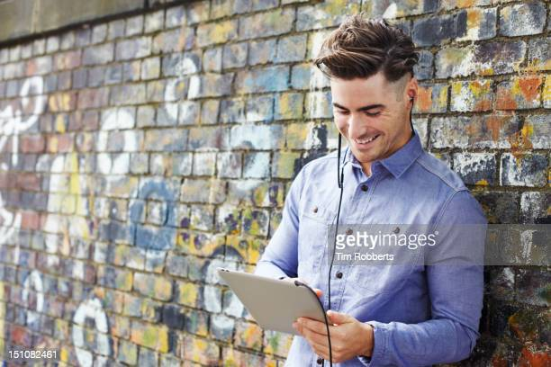 Man using digital tablet with headphones.
