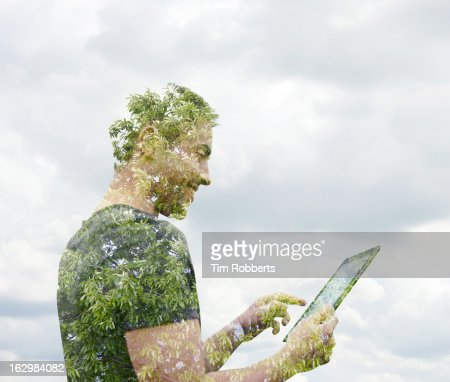 Man using digital tablet with tree.