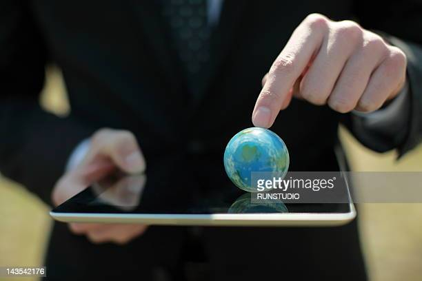 Man using digital tablet&Globe