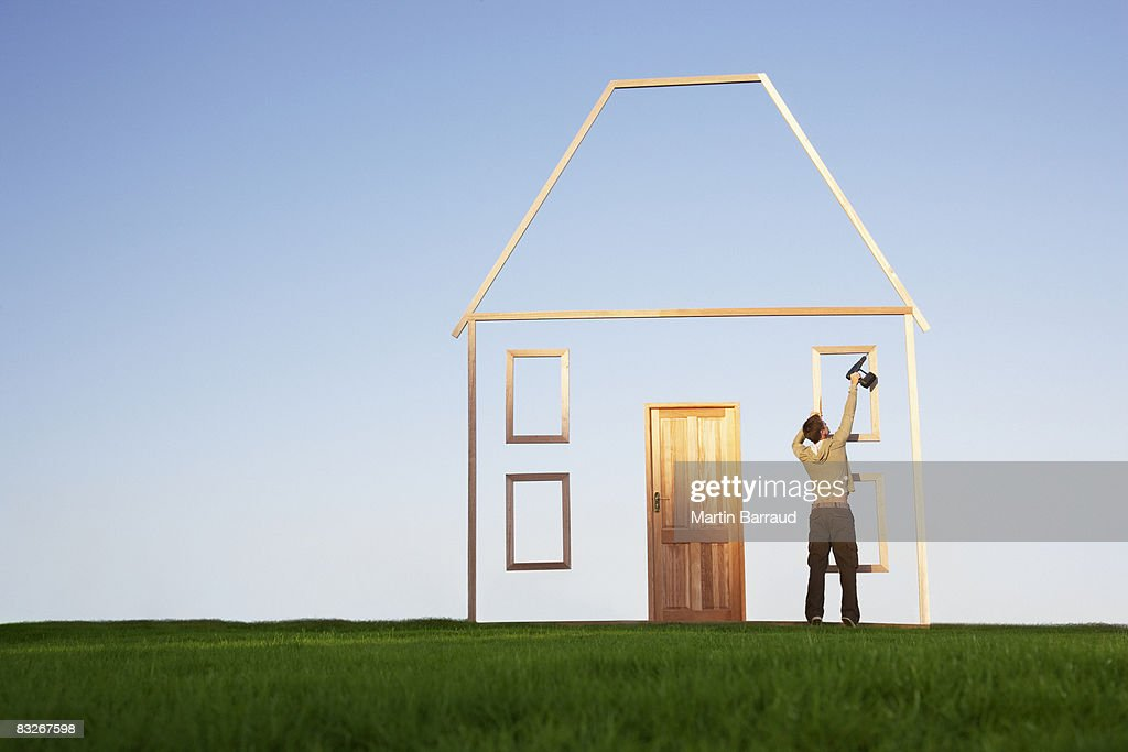 Man using drill on house outline : Stock Photo