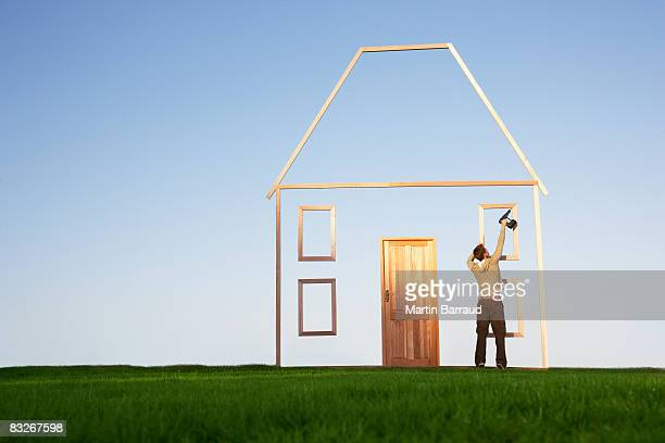 Man using drill on house outline