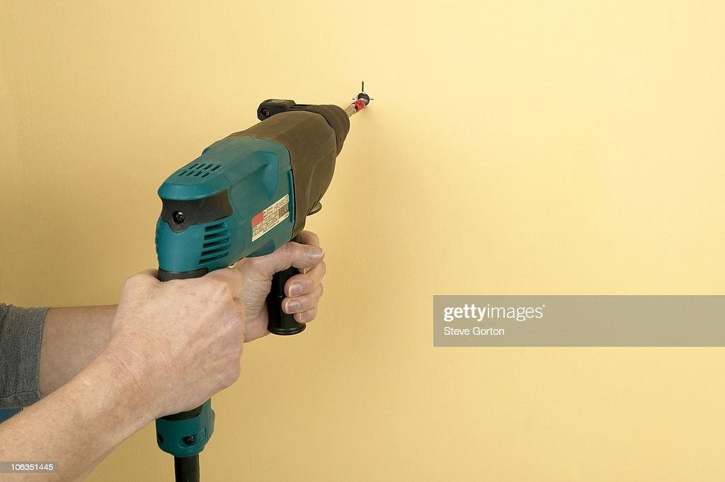 man using drill to make hole in wall stock photo getty images. Black Bedroom Furniture Sets. Home Design Ideas