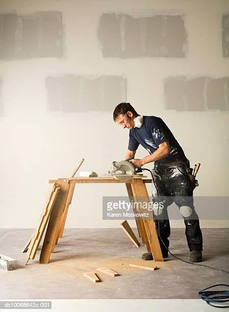 Man using electric saw to cut wood