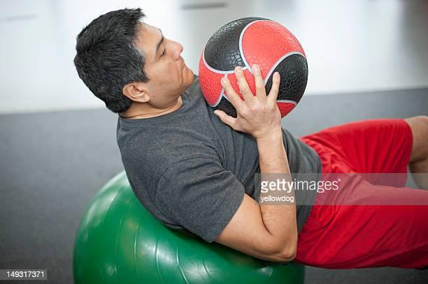 Mann mit Fitness-ball im Fitness-Center