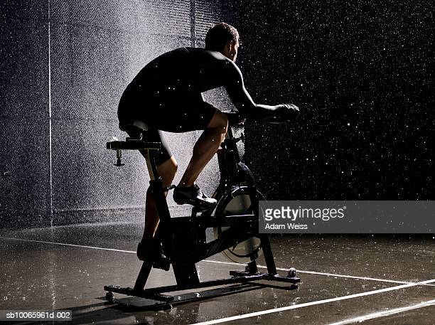 Man using exercise bike in basketball court at night