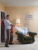 Man using fire extinguisher on arm chair on fire