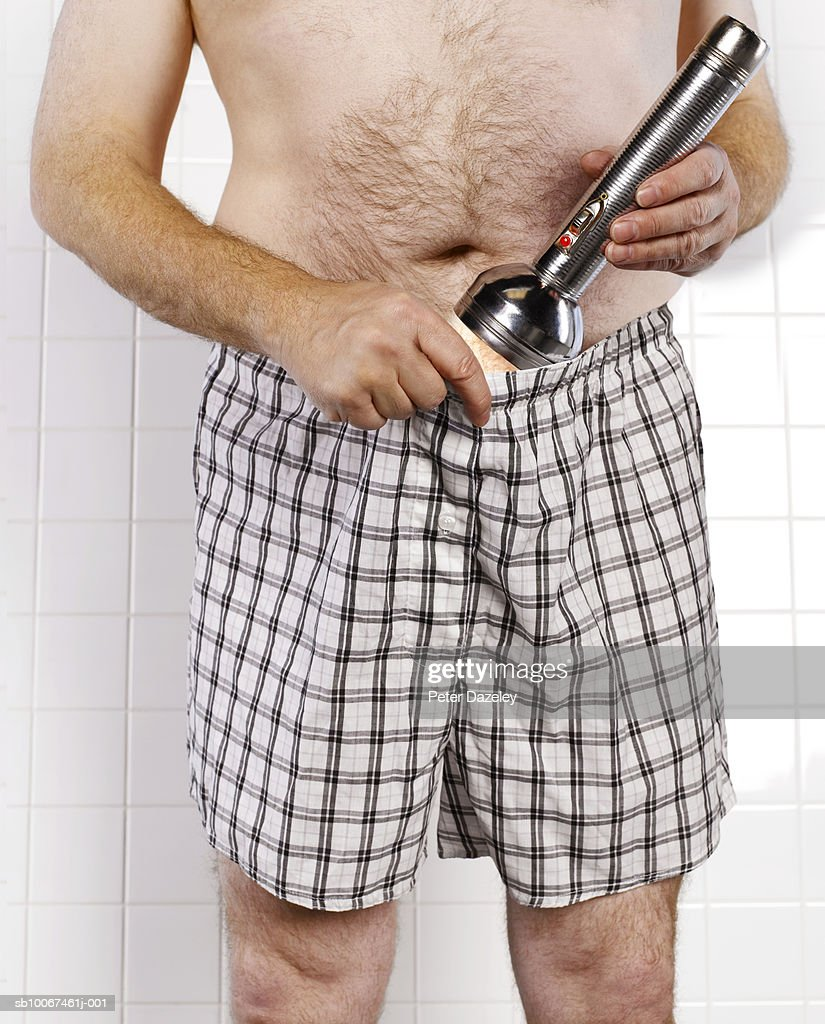 Man using flashlight to examine testicles, mid section, close-up : Stock Photo
