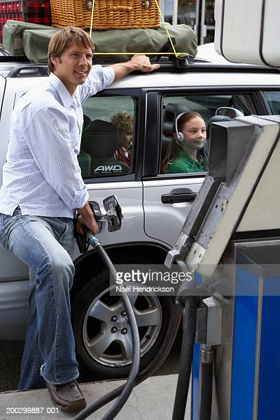 Man using fuel pump, daughter and son (5-8 years) waiting in car