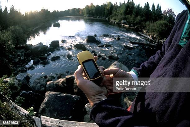 Man using GPS on river, Maine.