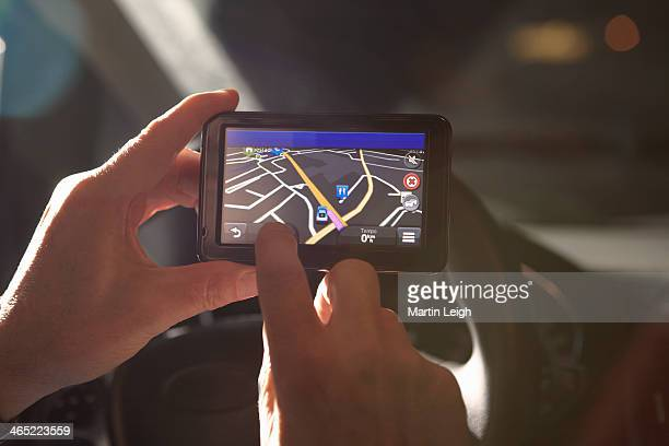 man using gps sat nav at night in car