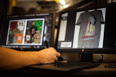 Man using graphic tablet and pen to design t-shirt