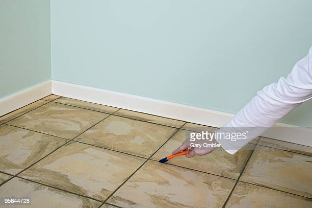 Man using grout shaper at edge of floor tile to make smooth finish
