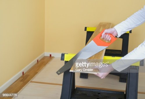 Man Using Hand Saw To Cut Through Piece Of Laminate