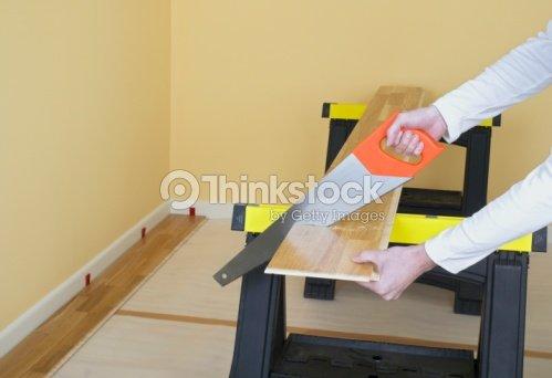 Man Using Hand Saw To Cut Through Piece Of Laminate Flooring On