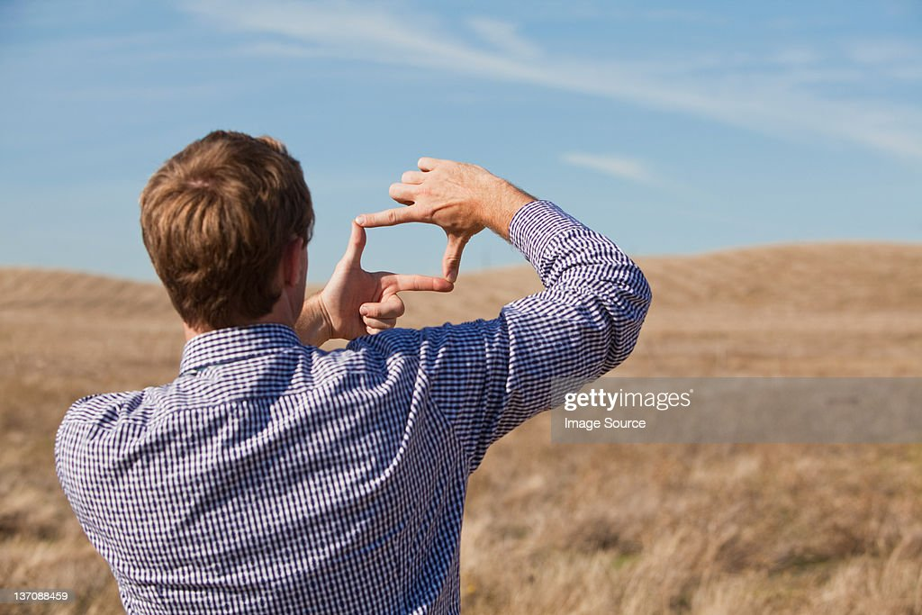 Man using hands to frame landscape : Stock Photo