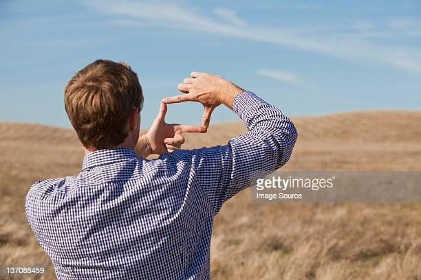 Man using hands to frame landscape