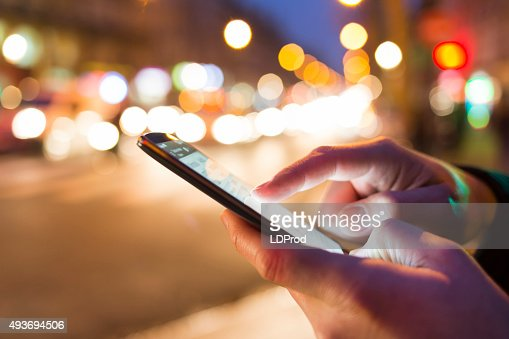 Man using his Mobile Phone in the street, bokeh : Stock Photo