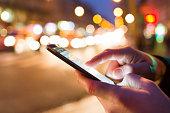 close up of male hands nightlight smartphone