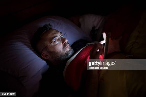 Man using his smart phone in the dark