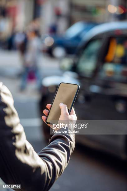Man using his smart phone on the street for calling a taxi through the app