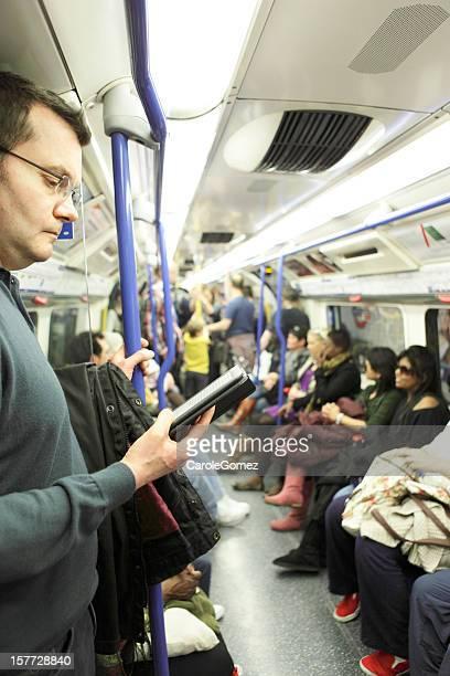 Uomo Kindle metro per Londra con il treno della metropolitana