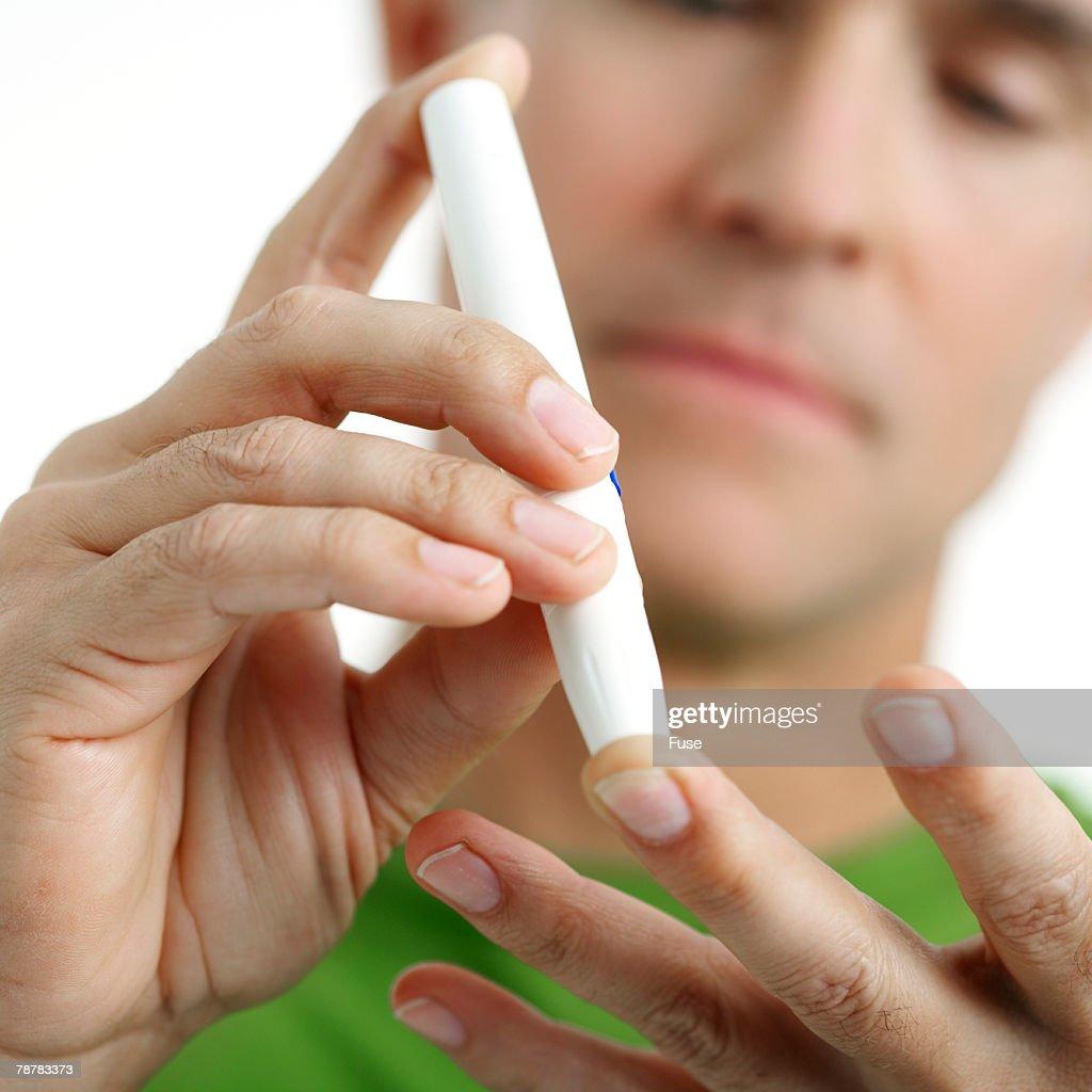Man Using Lancing Device on Finger