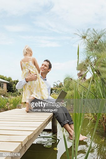 Man using laptop and embracing daughter (4-5) on jetty : Foto stock