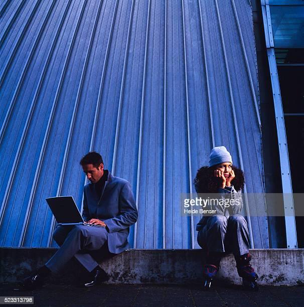 Man Using Laptop and Sad Businesswoman