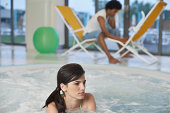 Man using laptop as he sits by pool, woman in pool by herself