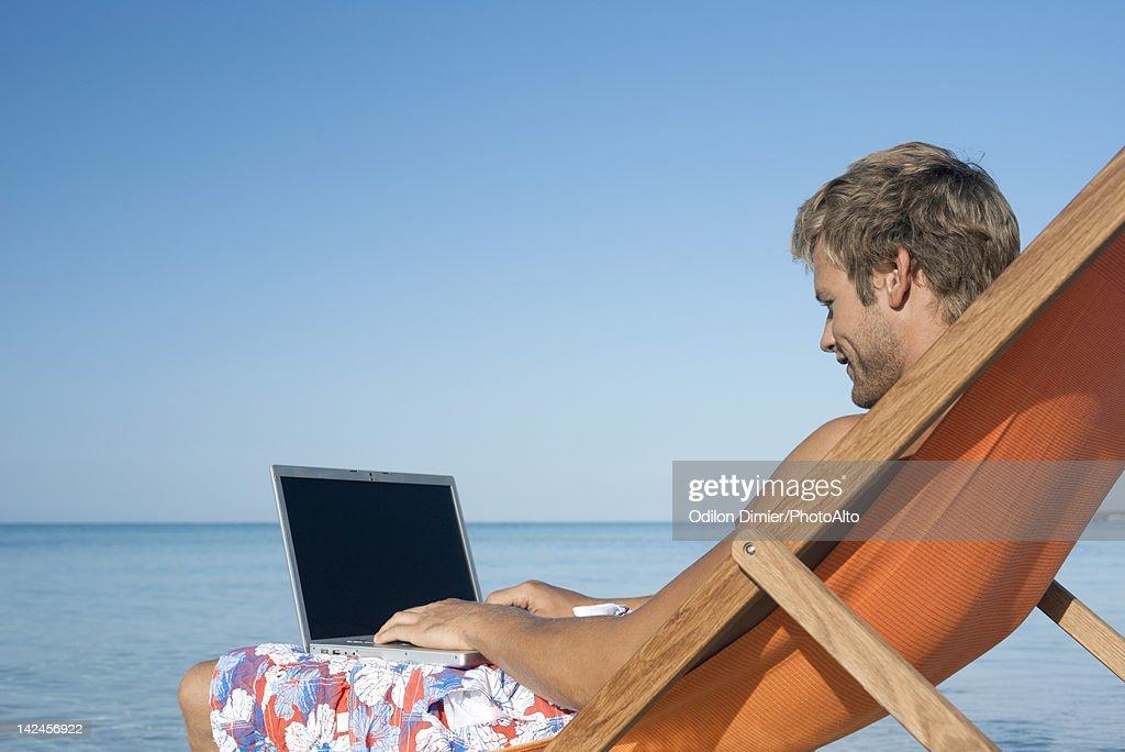 Man using laptop computer at the beach : Stock Photo