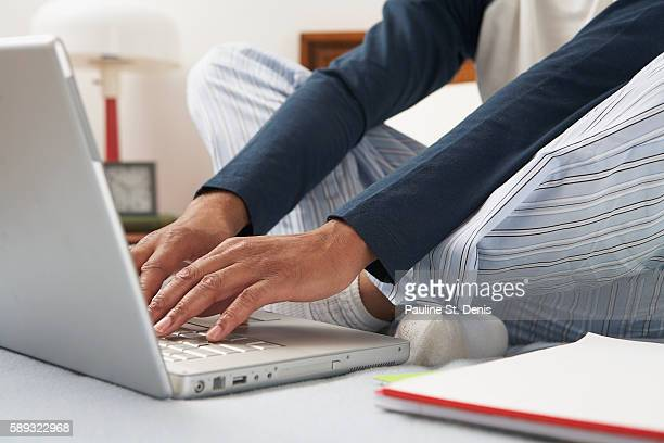 Man using laptop computer in bed
