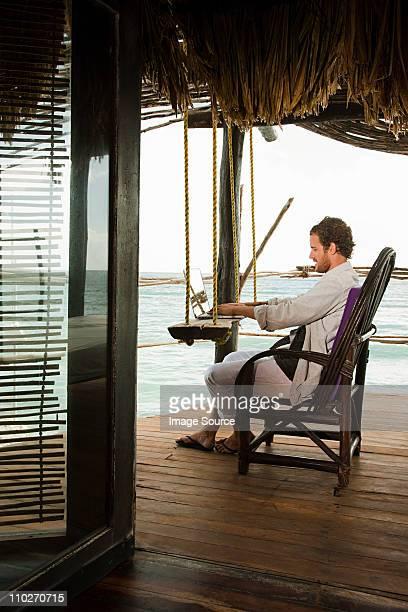 Man using laptop in beach hut