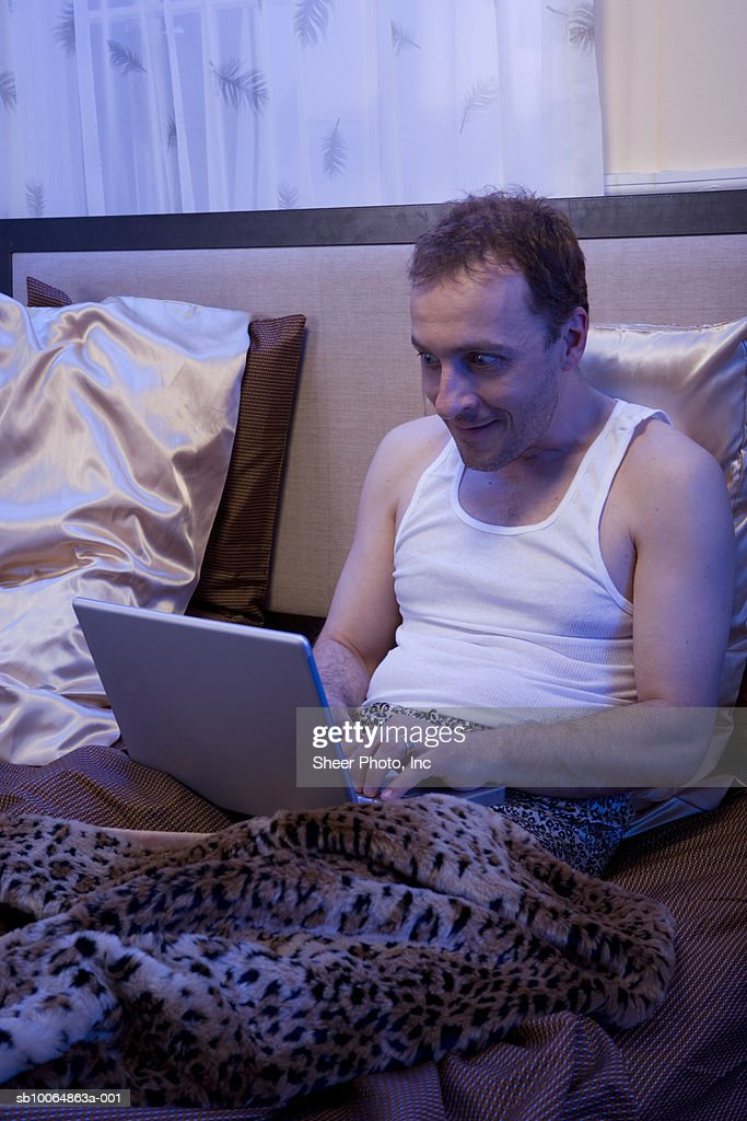 Man using laptop in bed : Stock Photo